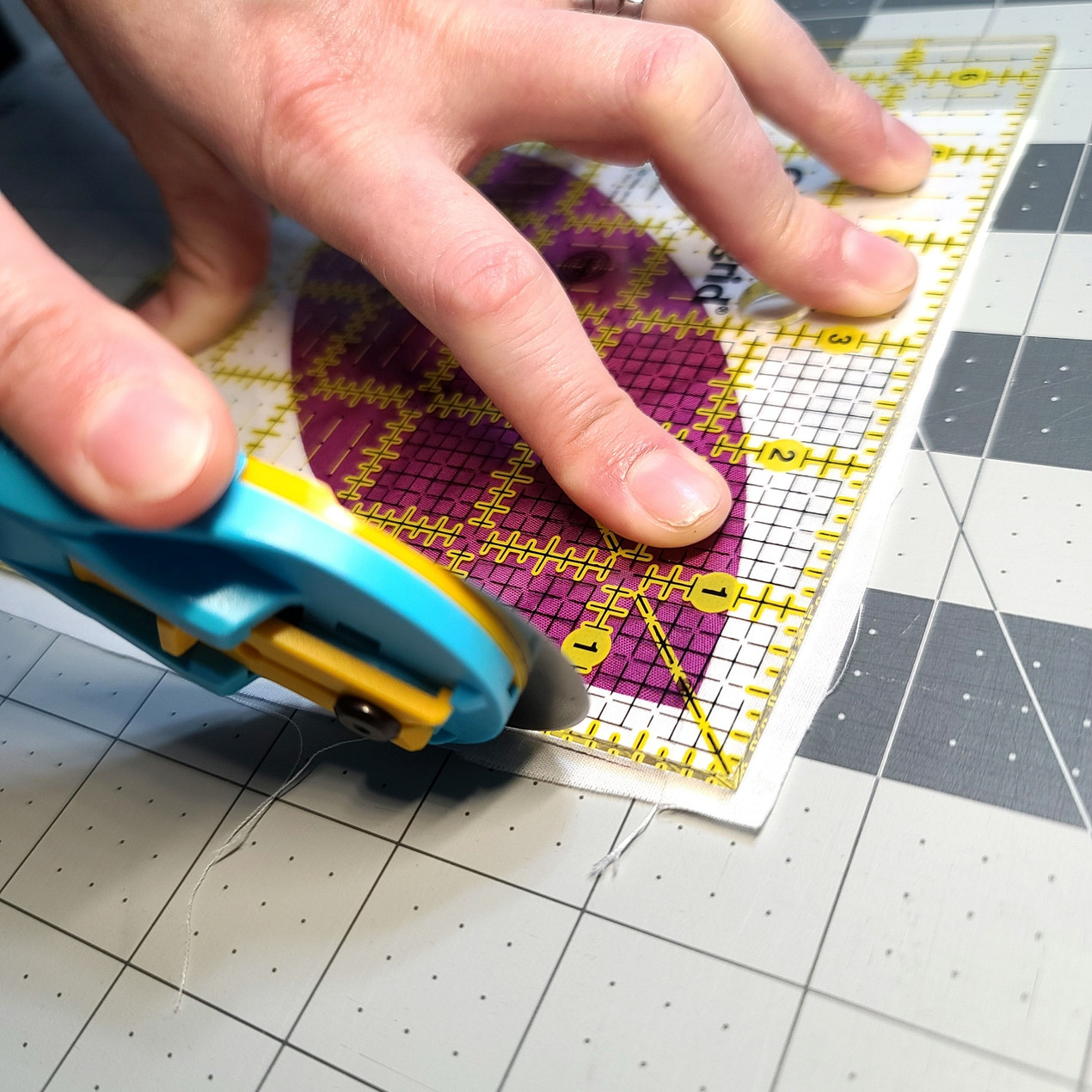A rotary cutter trimming a quilt block