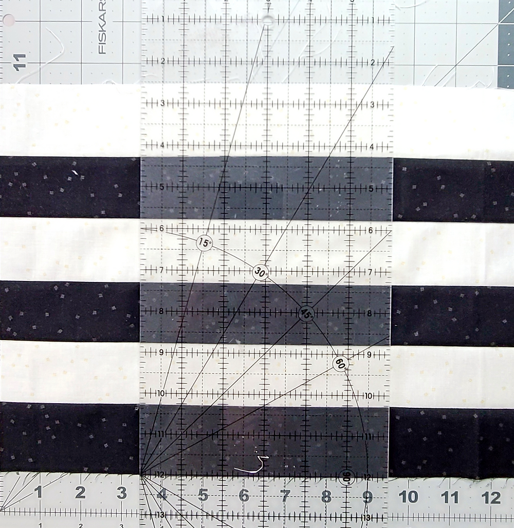 A long narrow quilting ruler over the top of a long strip of fabric stripes