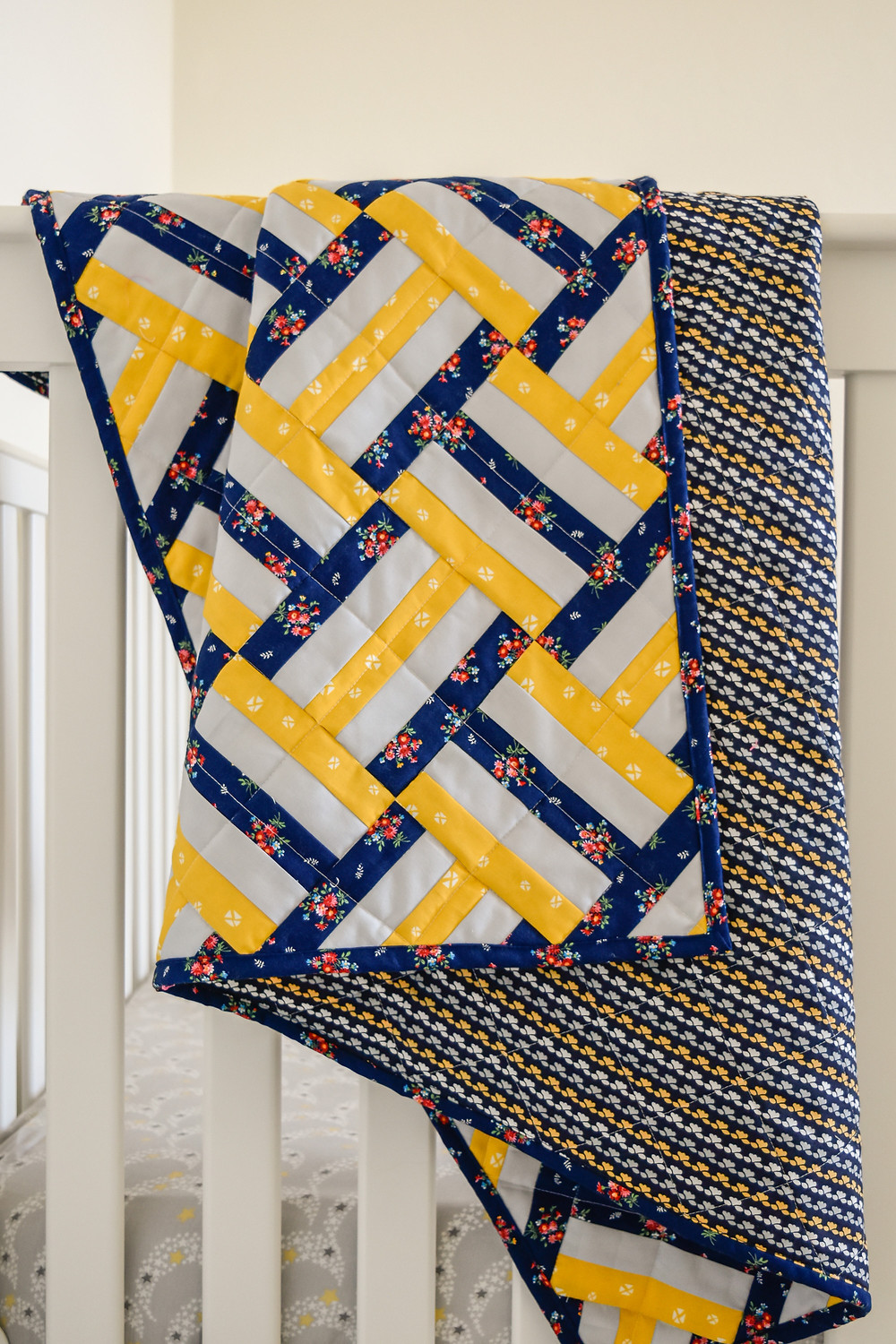 Blue yellow white weighted quilt on a crib rail