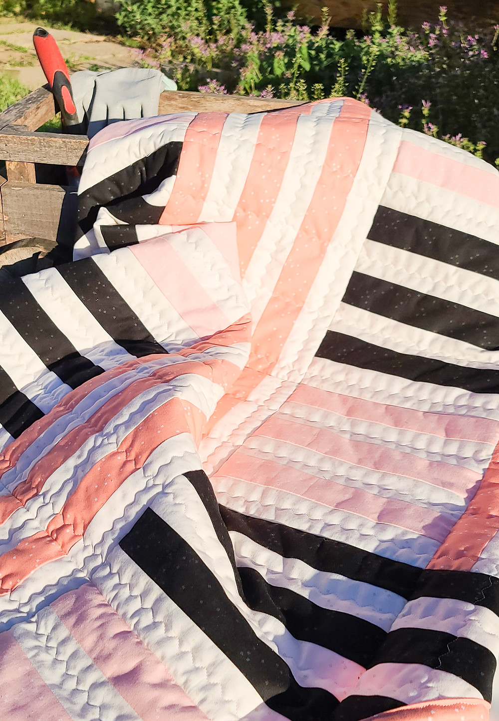 The warm morning sun shining on qult made of cream, black and peach tones arranged in a woven pattern. The quilt is laying in the garden next to a pair of gloves and a small shovel.