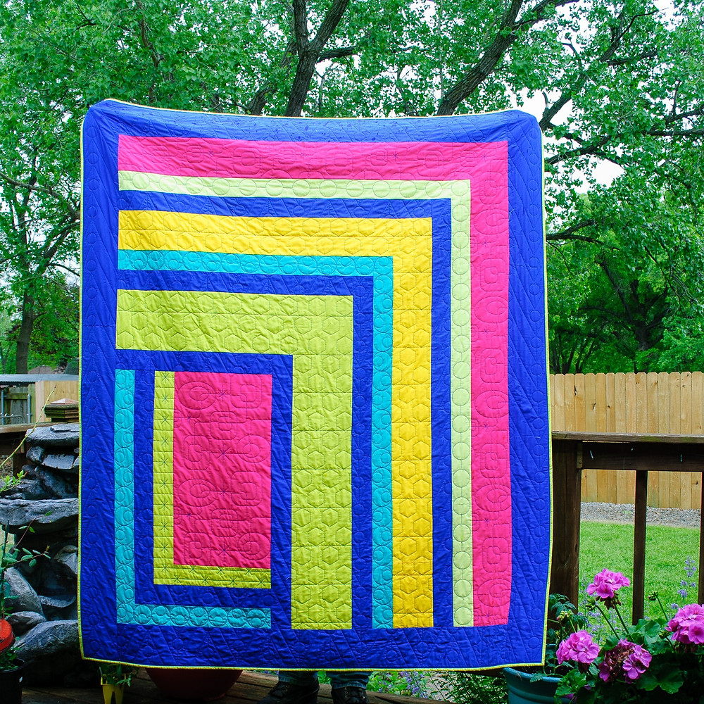 A bright modern quilt in blue pink green yellow in a log cabin design