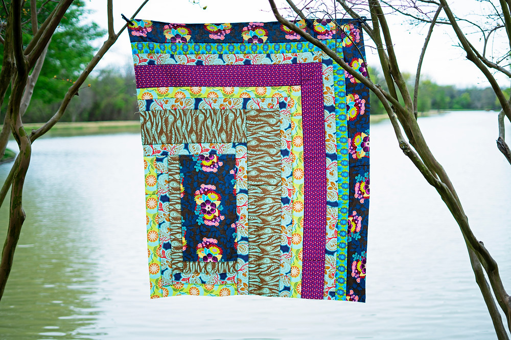 A colorful print version of Mod Cabin Quilt hanging from a limb over a body of water