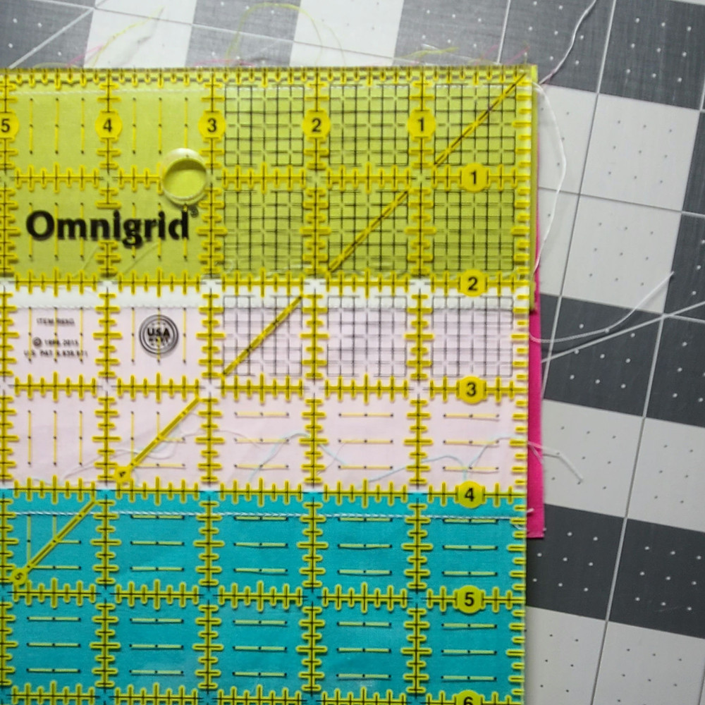 A quilting ruler placed on the backside of a quilt