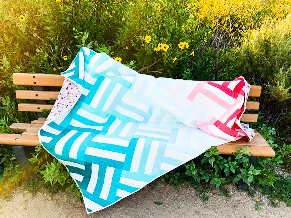 Pink blue green weighted quilt on a bench
