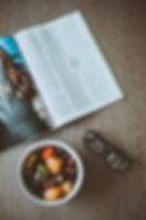 eyeglasses-beside-bowl-of-food-and-magaz