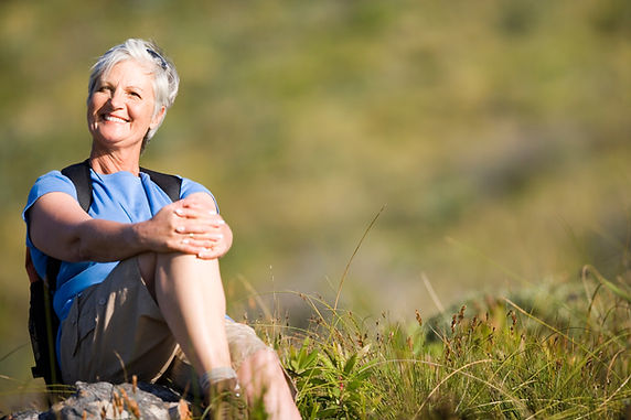Mature woman resting on hiking along mou