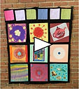 quilt on wall pic with play arrow.jpg