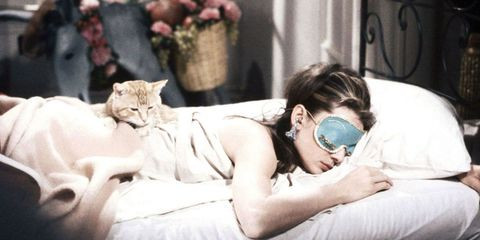 Audrey Hepburn sleeping with cat on her back.