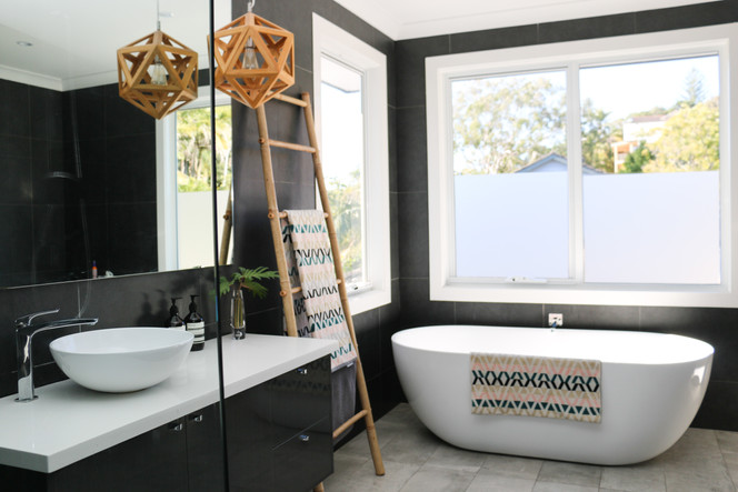 freshwater contemporary build. Dark grey bathroom with freestanding bath. Timber pendant.