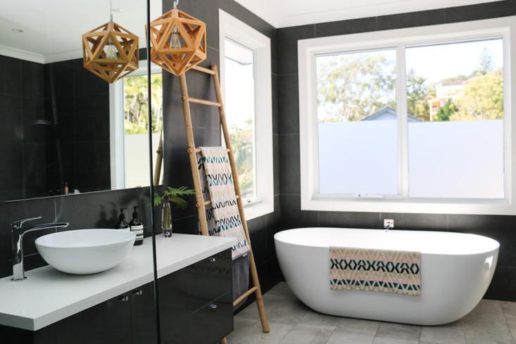 freshwater contemporary build. Dark grey bathroom with freestanding bath. Timber pendant.