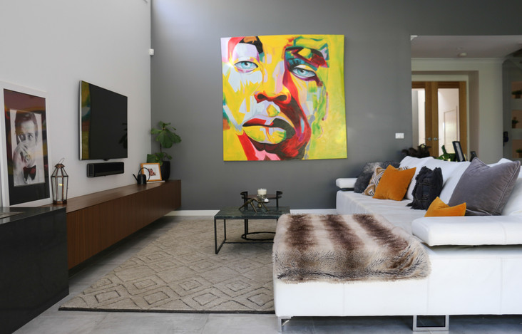 freshwater contemporary new build. living room with timber cabinetry, Armadillo Gazelle rug. Abstract painting. White leather sofa. Fur throw.