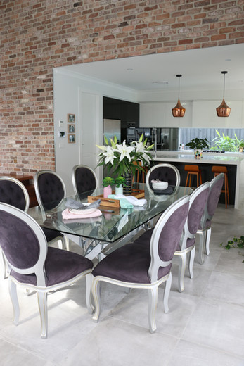 Freshwater - contemporary/industrial dining room with glass table and black chairs.