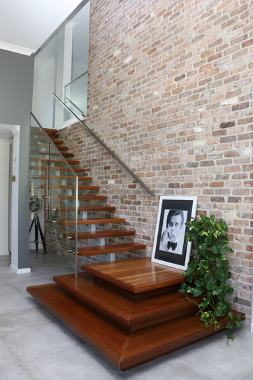 Freshwater - contemporary living room with feature timber floating staircase against exposed brick feature wall.