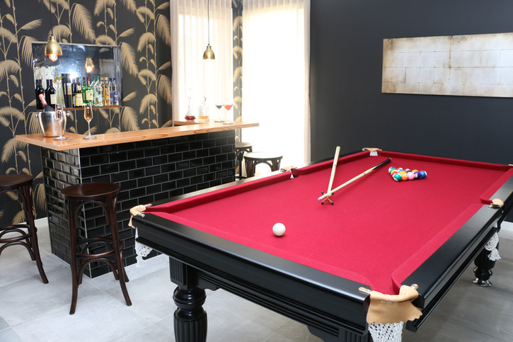 Freshwater - contemporary/industrial dark moody bar/pool room. Black walls and tan leather sofa.