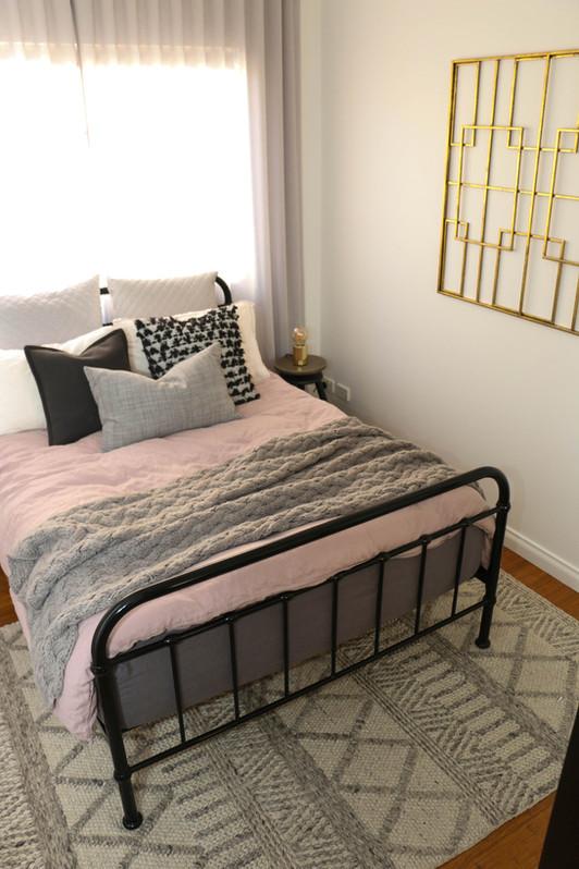 manly guest bedroom - modern industrial - grey pink, brass artwork, black metal bed