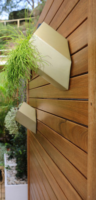 courtyard with timber feature wall and brass planter.