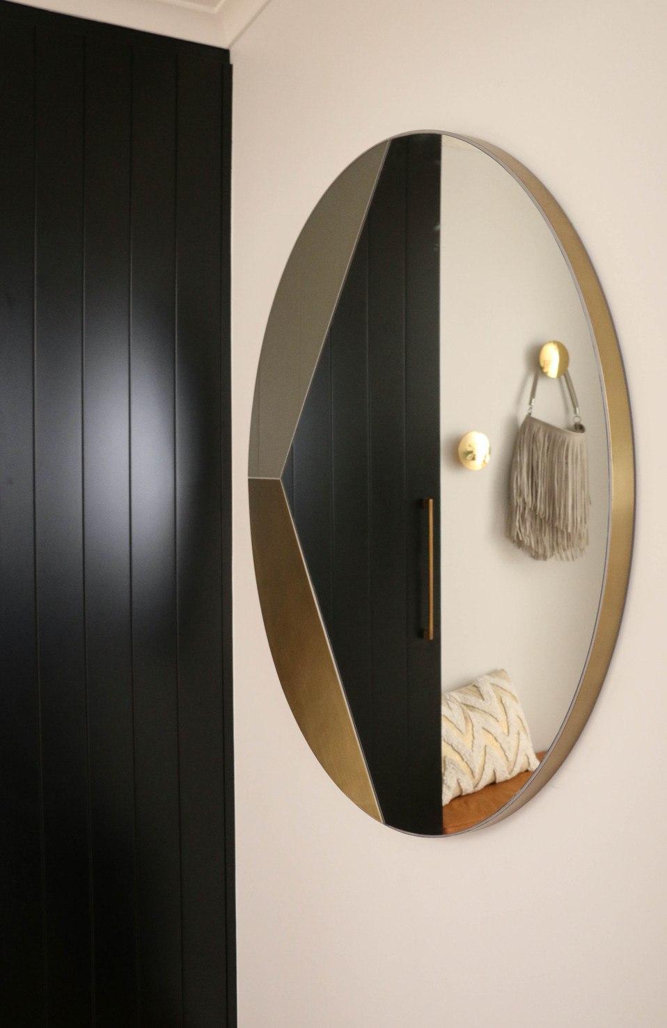 manly entrance - black custom cabinetry with brass round mirror