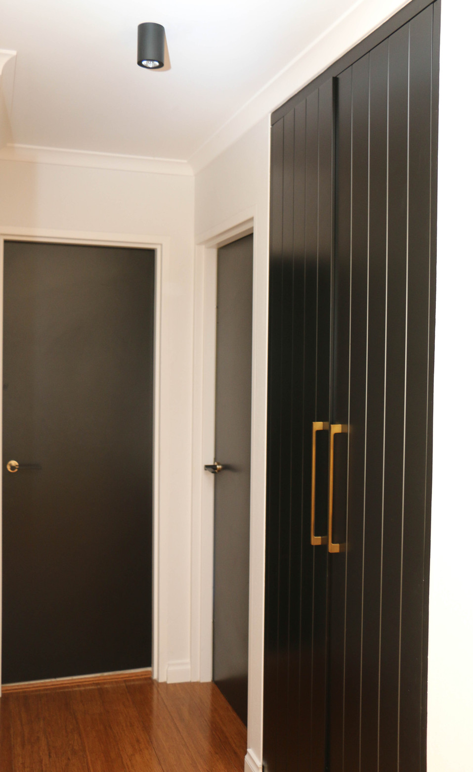 manly hallway - black custom cabinetry with brass handles