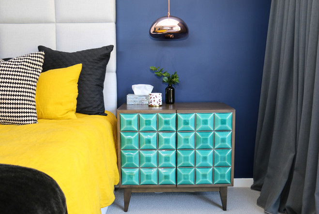 freshwater contemporary new build. Master navy bedroom. Bold mustard linen bedding. Fabric bedhead. Bold brigh artwork. Black leather bedend. Green tiled bedside tables. Copper pendant lights. Grey linen curtains.
