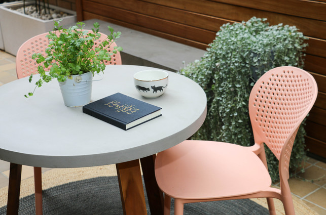 Outdoor seating area - concrete round table with pink chairs