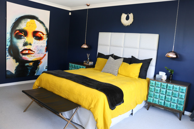 freshwater contemporary new build. Master navy bedroom. Bold mustard linen bedding. Fabric bedhead. Bold brigh artwork. Black leather bedend. Green tiled bedside tables. Copper pendant lights.