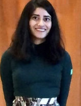 Huda wearing a turqoise turtle neck, smiling, and standing against a brown-coloured background
