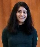 Huda porte un pull à col roulé turquoise, elle sourit et se tient debout devant un arrière-plan de couleur marron