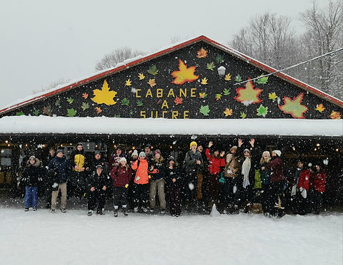 A group of youth in winter attire are standing in front of a building with a triangular roof that says 'Cabane A Sucre'. It is snowing and there are maple leafs drawn on the building.