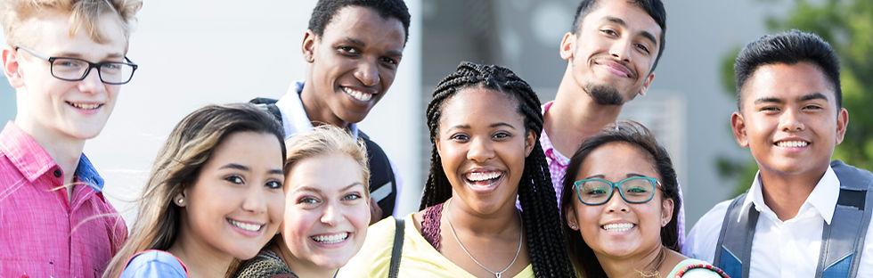 Un groupe de jeunes sourient et font face à l'appareil photo, et se tiennent debout dehors.