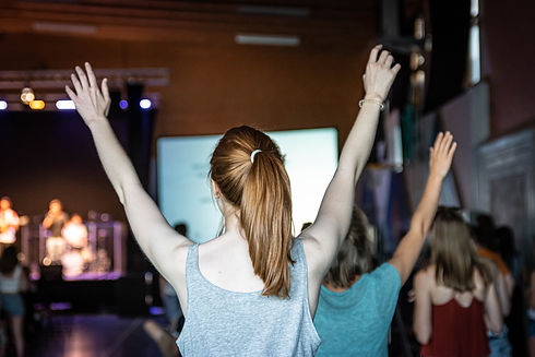 Young woman is worshipping at a service in a church.jpg