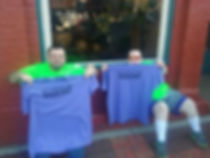 Two men hold up T-shirts with Angola Motorsports Speedway logo
