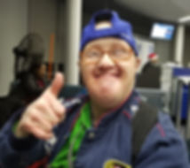 A man wearing glasses and backwards cap smiles and gives thumbs up