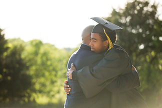 Stock photo of a man wearing his cap and gown hugging his father