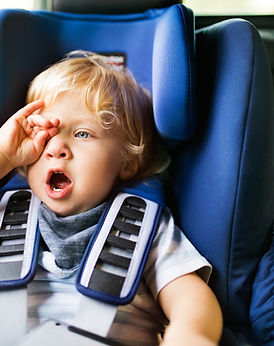 Toddler in carseat yawning and rubbing eye