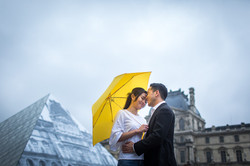couple with umbrella at le louvre