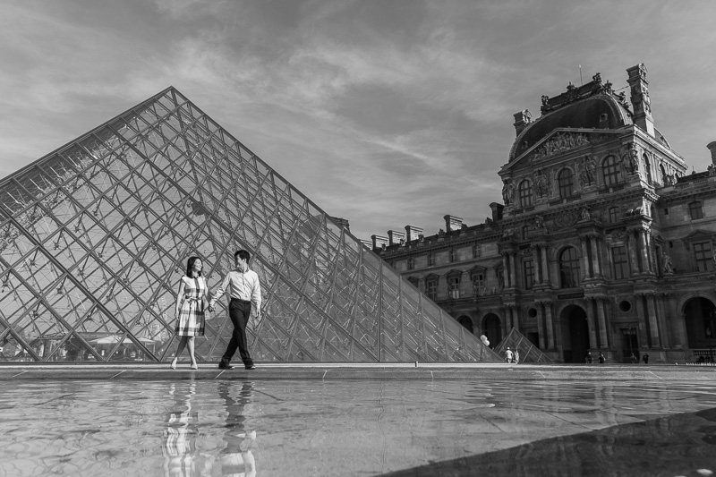 Couple walks at le Louvre courtyard