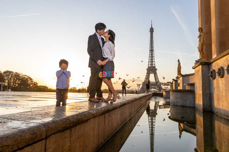 Parents are kissing in front of the Eiffel tower