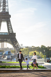 family is walking in front of the Eiffel tower
