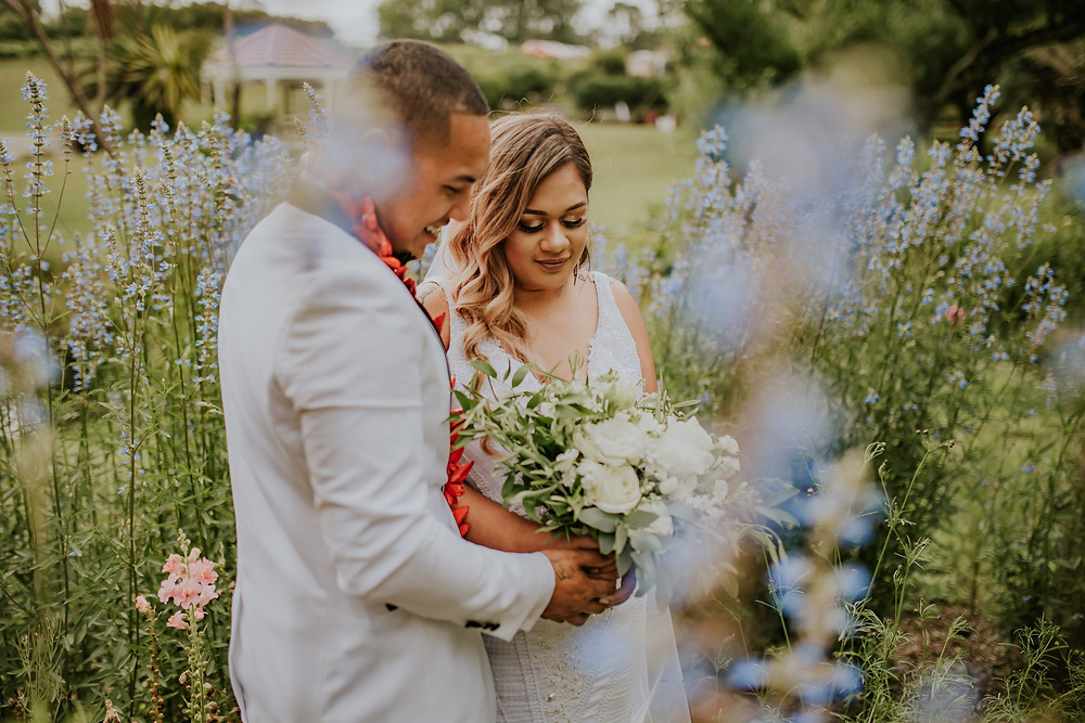 A bride and groom stand in a field of blue flowers
