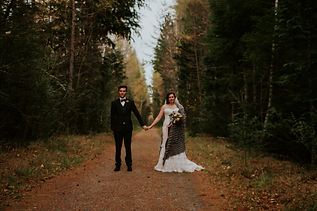 A newly married couple hold hands on a path in the forest. They are lined by trees on either side.