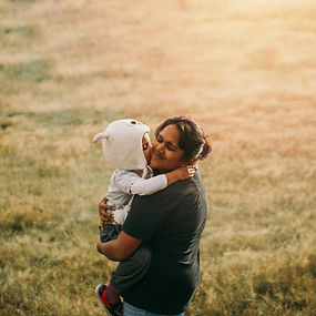 Photographer Samantha Ram holding young child in field at sunset. The child is kissing her on the cheek.