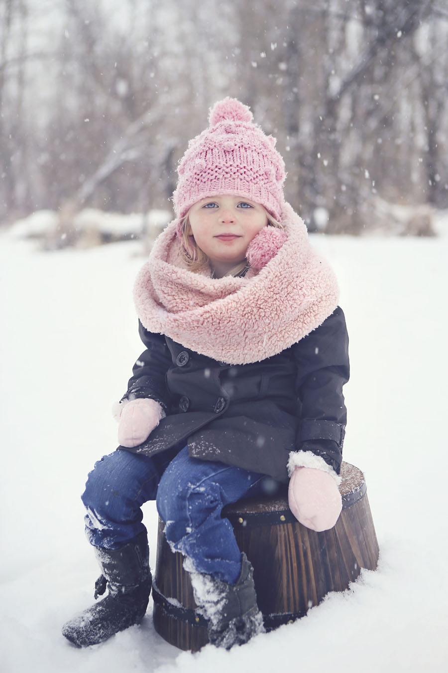 Child on barrel in snow