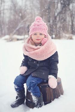 Child on barrel in snow