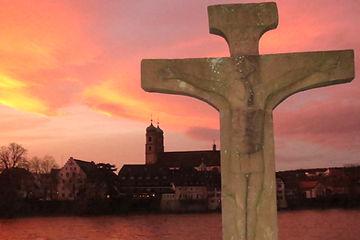sunset over Rhine River, cross and Catholic Church, Bad Sackinton Germany Switzerland