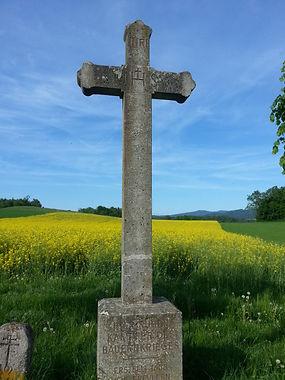 Croix catholique de campagne suisse avec des fleurs en arrière-plan