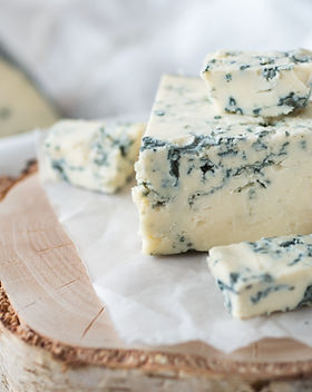 Tasty blue cheese on a wooden background