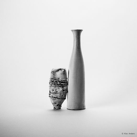A white vase a an object that leans against it.