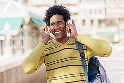 vecteezy_black-man-listening-to-music-with-wireless-headphones-sightseeing_3015426_edited.