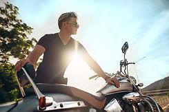 vecteezy_motorcyclist-stands-next-to-bike-backlit-by-sun_1223962.jpg