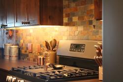 earth tone stone backsplash in a kitchen above the stove